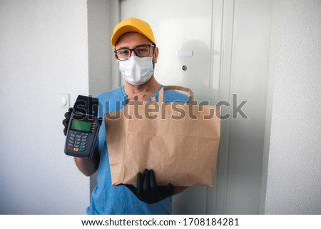 Delivery guy with protective mask holding box / bag with groceries and POS for contactless payment. #1708184281