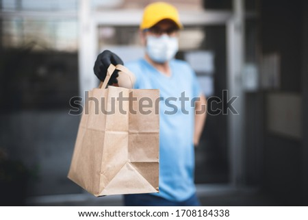 Delivery guy with protective mask and gloves holding box / bag with groceries in front of a building. #1708184338