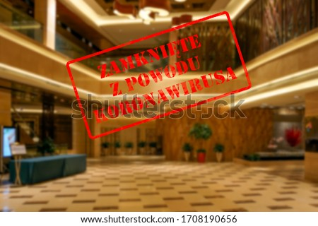 Defocused view of interior of upmarket hotel reception or hall, empty and closed due to covid 19 pandemic with Polish notice Closed due to Coronavirus #1708190656