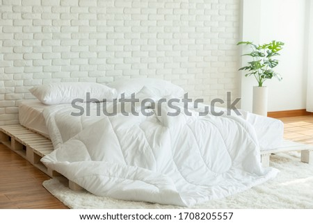 Messed bed with white pillow and blanket with natural light in bedroom in the morning,Messy bed after wake up,Messy bed and Cozy Bedroom Concept #1708205557