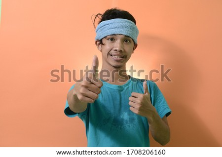 Portrait of a funny man giving a thumbs up, man wearing a blue shirt with a towel on his head, orange background  #1708206160