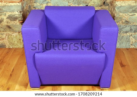 Comfortable and stylishly designed blue office chair in front of a wall #1708209214