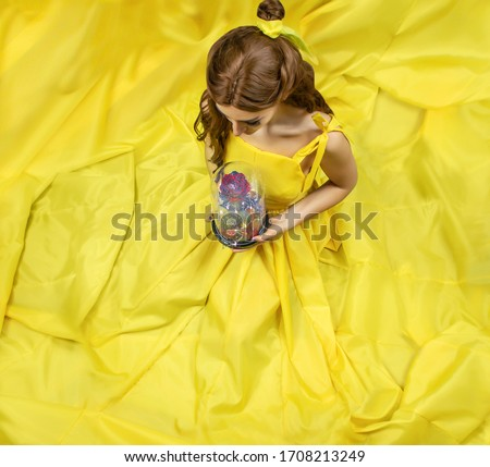 Pretty woman in the yellow long dress closeup with red rose in her hands. Beauty and the beast cosplay Royalty-Free Stock Photo #1708213249