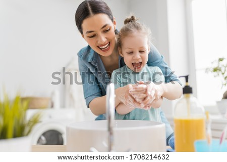 A cute little girl and her mother are washing their hands. Protection against infections and viruses.    #1708214632