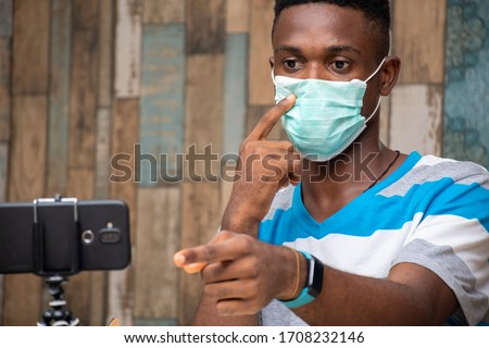 young black man working from home wearing a face mask, vlogger working at home, creating content #1708232146