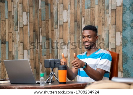 young man making a vlog, interacting with viewers, working from home, doing a live video chat #1708234924