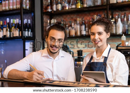Happy young waiter making notes in notepad while his pretty colleague with touchpad standing near by and both looking at you Royalty-Free Stock Photo #1708238590