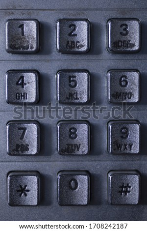 Close up of a dirty public telephone metal keypad. Macro view of the buttons and digits of a public phone keypad. Royalty-Free Stock Photo #1708242187