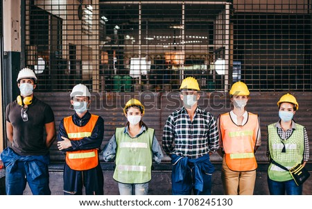 Group of industrial or engineer corporate workers wear protective mask and hard hat helmet standing line up in front of factory lock down prevention for Coronavirus or COVID-19 epidemic outbreak #1708245130