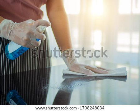 COVID-19 prevention sanitizing inside. Cleaning home table sanitizing kitchen table surface with disinfectant spray bottle washing surfaces with towel and gloves. Royalty-Free Stock Photo #1708248034