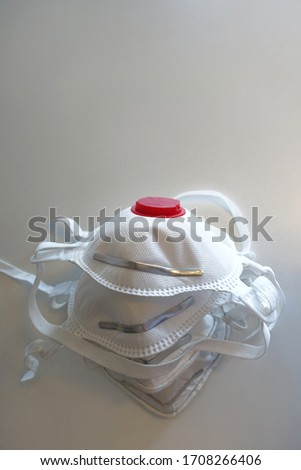 Four stacked anti virus face masks with filters, close up. White reusable face masks with exhalation vents on table. Anti air pollution face masks. White background. #1708266406