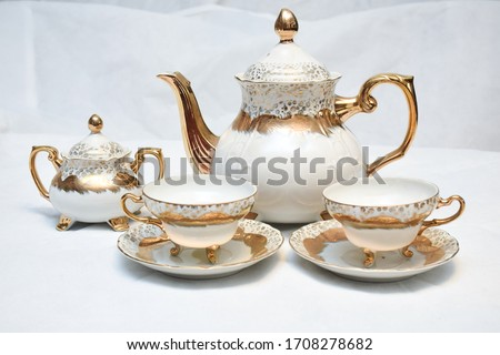 Mock up / design set of elegant and traditional teapot colorful white blue gold coffee cup & Tea cup on cup's plate beside the hot tea pot , design/ drink-ware isolated on white background