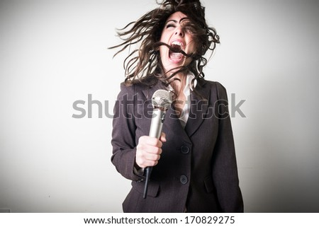 singing beautiful young businesswoman on gray background #170829275