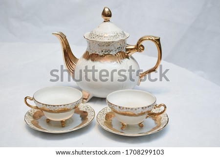 Mock up / design set of elegant and traditional teapot colorful white and Gold coffee cup & Tea cup on cup's plate beside the hot tea pot , design/ drink-ware isolated on white background