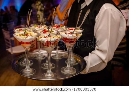 Cup of dessert is the strawberry on a tray that is carried by the water. Sweet treats to be served after dinner, at a party with cream and berries. #1708303570