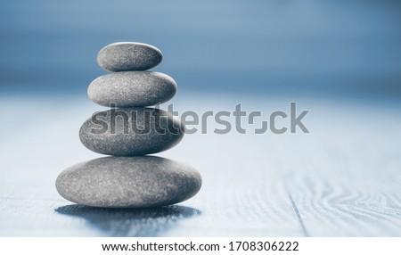 Stack of Zen Stones on blue background.