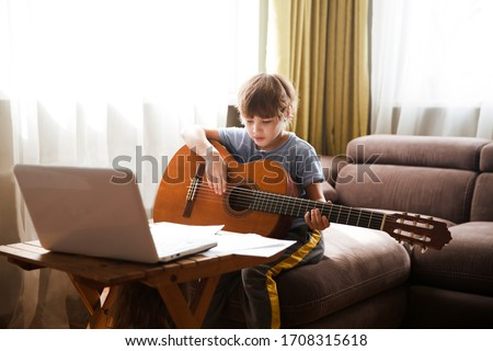 Kid  boy playing  guitar and watching  online lessons  on laptop while practicing at home.  Stay home. quarantine. Online training, online classes.  #1708315618