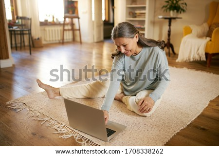 Indoor image of beautiful energetic female on retirement sitting barefoot on floor using laptop turning on calm music for meditation. Elderly European woman surfing internet on portable computer #1708338262