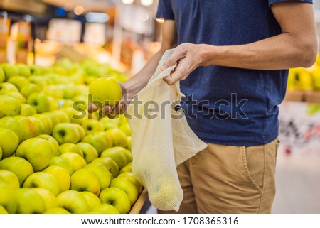Man chooses apples in a supermarket without using a plastic bag. Reusable bag for buying vegetables. Zero waste concept #1708365316