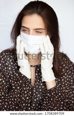 portrait of beautiful young woman wearing cotton white mask and medical/surgical gloves on white background.  #1708389709