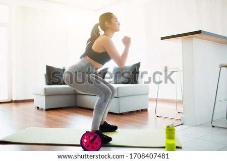 Young woman doing sport workout in room during quarantine. Doing squat exercise on yoga mat in room. Concentrated workout. #1708407481