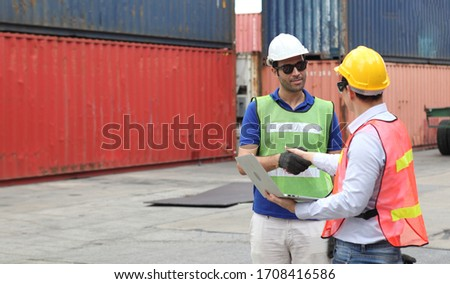 Engineering group working and they are loading container for support logistics and import export business #1708416586