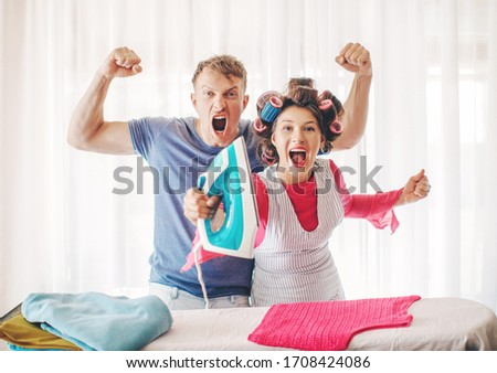 A family woman is ironing clothes at home. Young couple ironing together isolated on white background. Romance lovers. Life. Smiling man and woman. Honeymoon. Romantic lovers. People. Crazy. Funny.