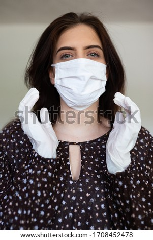 portrait of beautiful young woman wearing cotton white mask and medical/surgical gloves on white background.  #1708452478