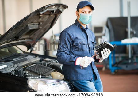 Masked car mechanic holding a jug of motor oil during coronavirus pandemic Royalty-Free Stock Photo #1708466818