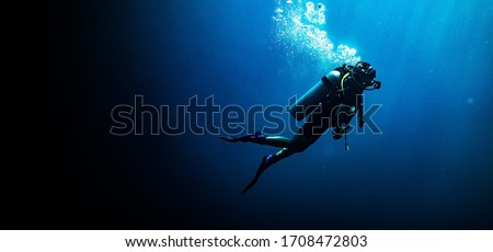 Woman scuba diving in deep blue sea banner on black background Royalty-Free Stock Photo #1708472803