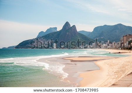 Ipanema Beach, in Rio de Janeiro, Brazil, totally deserted during the pandemic of the new Corona virus. Morro Dois Irmaos with a beautiful blue sky, clear sand and sea with shades of blue and green. Royalty-Free Stock Photo #1708473985