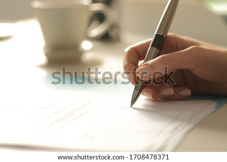 Close up of woman hands signing contract sitting on a desk at night