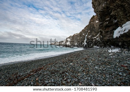 A pebble beach with a small curve. There's a rock face close to the ocean. There are gentlewaves gently rolling in on the beach. There's snow on the mountain.The sky is dramatic clouds with blue sky. #1708481590
