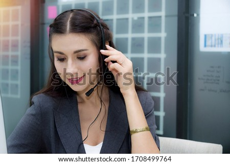 Attractive smiling caucasian woman call center with microphone headset offering customer service waiting to answer various problems about the product use and good after-sales service. #1708499764