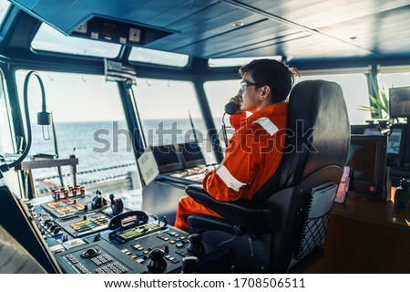 Filipino deck Officer on bridge of vessel or ship wearing coverall during navigaton watch at sea . He is speaking on GMDSS VHF radio, communication between vessels. Royalty-Free Stock Photo #1708506511