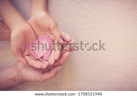adult and child hands holding intestine shape, healthy bowel degestion, leaky gut, probiotics and prebotics for gut health, colon, gastric, stomach cancer concept Royalty-Free Stock Photo #1708521940