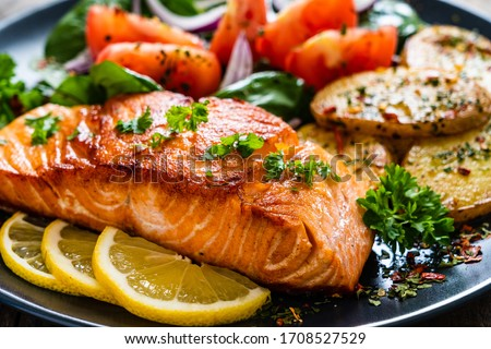 Fried salmon steak with potatoes and vegetables on wooden table Royalty-Free Stock Photo #1708527529