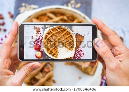 Make phone picture of food. Smartphone photo of apple pie dessert. Create blogging content. Vegan breakfast meal. Overhead.