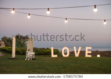 Decoration on a wedding - light sign love and white doors with a night view in the background