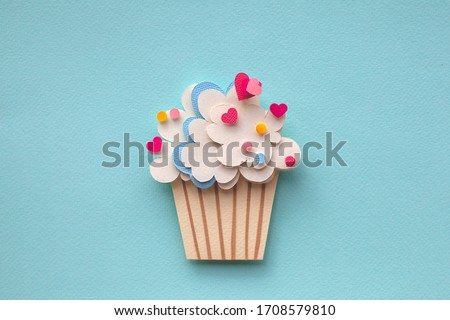 Paper cutting cupcake on blue background. Handmade art work. Colorful sprinkles (dot and star) for your birthday card design.