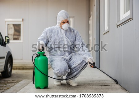 Man in virus protective suit and mask disinfecting buildings of coronavirus with the sprayer. Infection prevention and control of epidemic. World pandemic. #1708585873