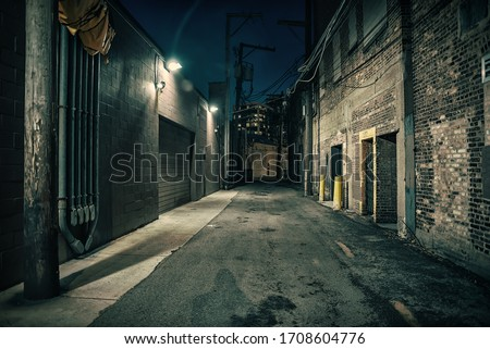 Dark and eerie urban city alley at night Royalty-Free Stock Photo #1708604776
