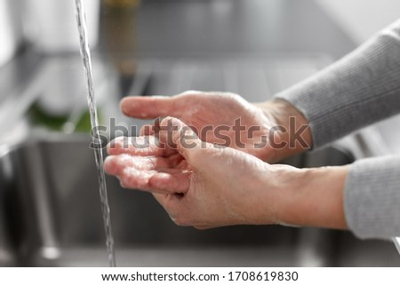 hygiene, health care and safety concept - close up of woman washing hands with soap and water in kitchen at home #1708619830