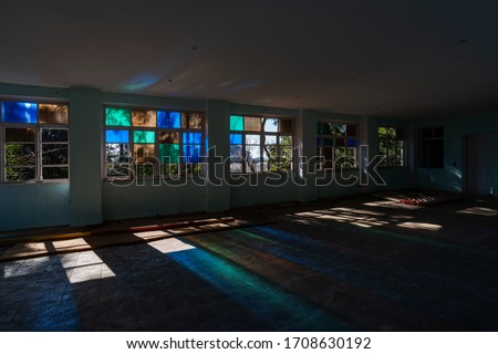 Multicolored sun rays on the floor of an abandoned building #1708630192