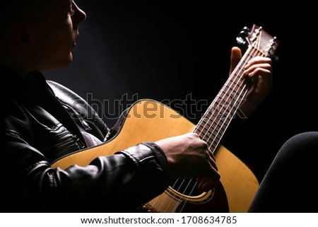 Young men playing the guitar with black background #1708634785