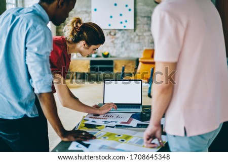Back view of crop multiethnic male and female employees in casual clothing standing and making business proposal together with blank screen laptop at stylish office  #1708645348