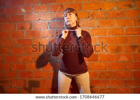 A middle-aged woman poses showing clothes near red brick wall. An inept model in non-professional shooting. Photography for sales turtleneck on the Internet or online store