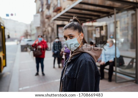Young woman wearing surgical mask outdoor at bus stop in the street #1708669483