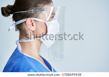 Portrait of female medical doctor wearing protective mask and face shield Royalty-Free Stock Photo #1708699438