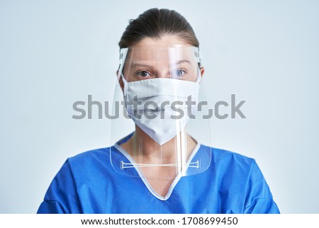 Portrait of female medical doctor wearing protective mask and face shield Royalty-Free Stock Photo #1708699450